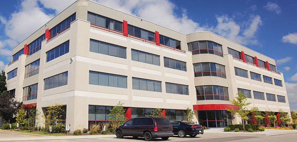 Ein vierstöckiges Bürogebäude mit Parkülätzen davor- Bürogebäude gehören auch zur Assetklasse im Portfolio von Zinshaus-Oberbayern