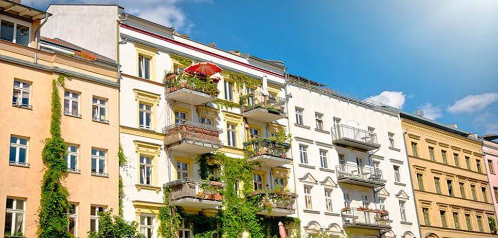 Eine Reihe mit bunten Mehrfamilienhusern mit Balkonen, Mehrfamilienhäuser gehören auch zum Assetclass im Portfolio von Zinshaus Oberbayern