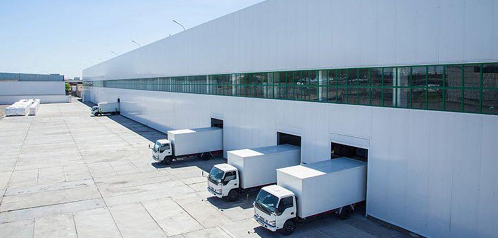 Weiße Logistikhalle mit vier LKW's beim Beladen- Logistikhallen gehören auch zur Assetklasse im Portfolio von Zinshaus-Oberbayern