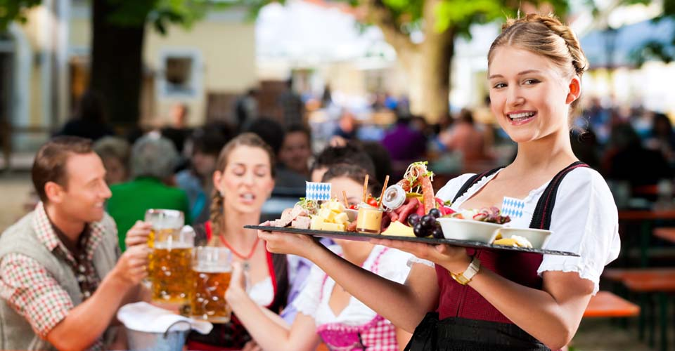 Eine Bedienung in Tracht serviert das Essen in einem Biergarten in München